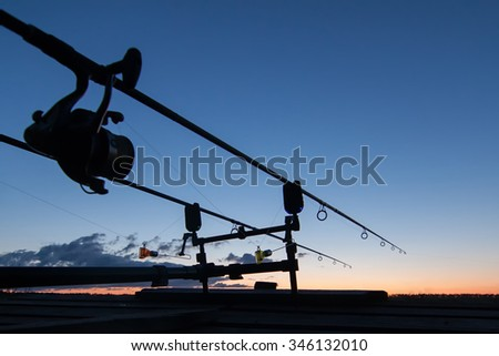 Fishing rods silhouette in the sunset light