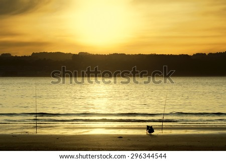 fishing rods with orange sky on the beach at dusk  - stock photo