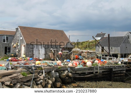 Fishing shacks with colorful buoys along the Atlantic Shore in Peggy's Cove, Nova Scotia, Canada, - stock photo