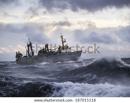 Fishing ship in strong storm. Sunrise.