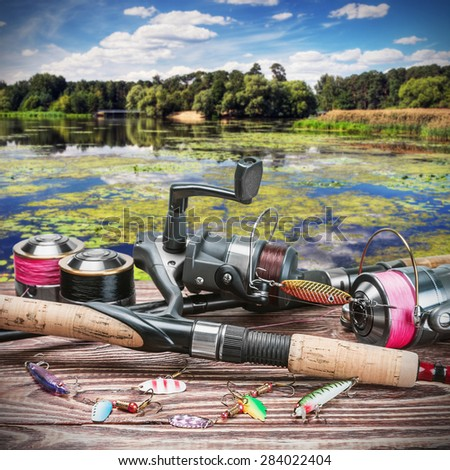 fishing tackle and accessories on the table against the background of a forest lake. Focus on spinning - stock photo