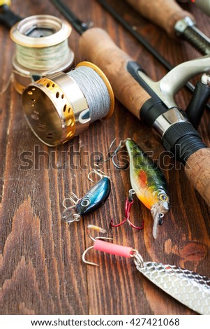 Fishing tackle - fishing spinning, fishing line, hooks and lures on wooden background - stock photo