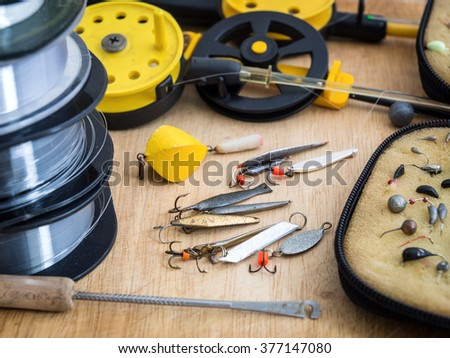 Fishing tackle for winter fishing on the wooden background - stock photo