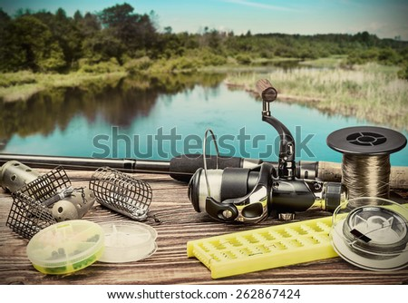 fishing tackle on a pontoon on the background of the lake in the woods. toning image - stock photo