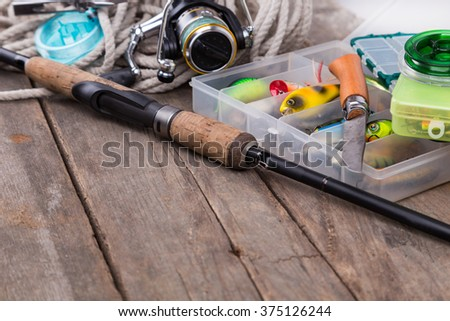 fishing tackles and baits in storage boxes with white cord and tools - stock photo