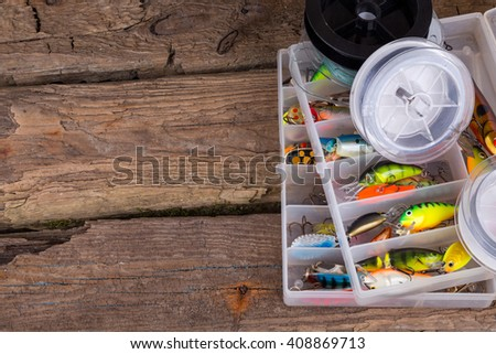 fishing tackles and fishing baits in box on vertical wooden board background. Design for outdoor sport business - templates, web, poster, card, advertisement.