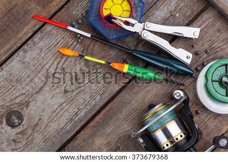 fishing tackles for anglers - swimmers, plummets and tools on wooden background - stock photo