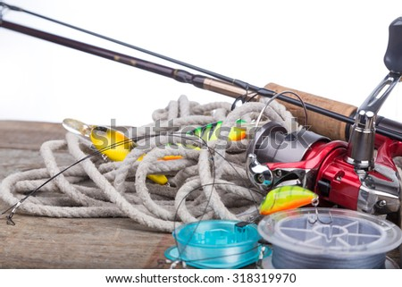fishing tackles reel, line and wobblers on wooden board with white background