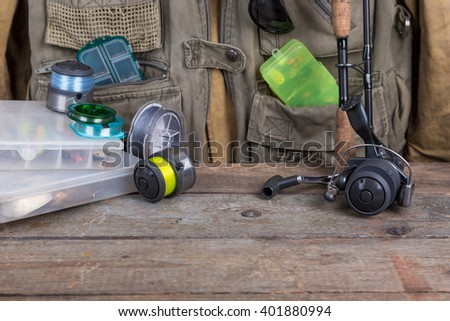 fishing tackles with fishing vest and wooden boards. design background for outdoor  advertisement, flayer etc. - stock photo