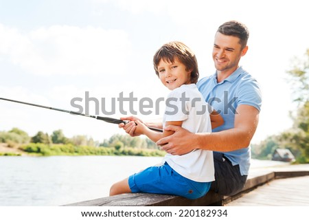Fishing together is fun. Cheerful father and son fishing together while little boy looking at camera and smiling - stock photo