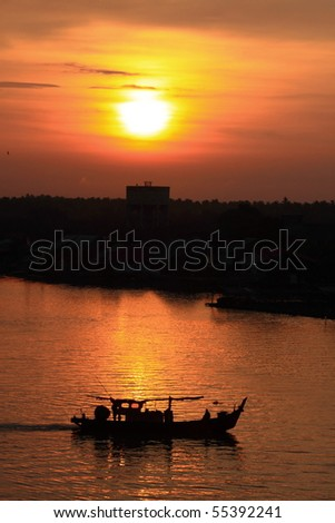 Fishing trawler on the water and dramatic clouds at sunrise - stock photo