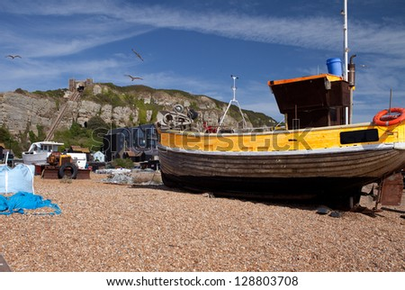 Fishing trawler or boat on beach in hastings with hill in background. yellow wooden ship and fishing industry