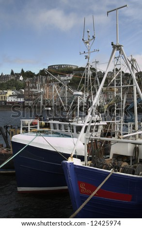 Fishing trawlers in Oban harbour with McCaigs Tower on hill - stock photo
