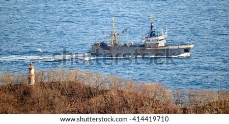 Fishing vessel returning to harbor safety under a menacing sky - stock photo