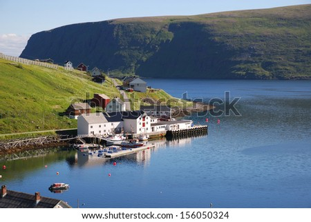 Fishing village is located on the side of blue fjord. Soroya is photographed in summer. There are lot of blue water and dark mossy cliff in the background. - stock photo