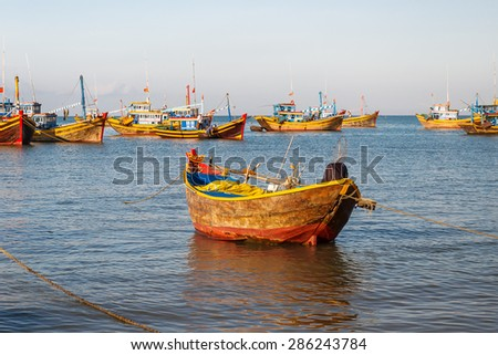 Fishing village, market and colorful traditional fishing boats near Mui Ne, Binh Thuan, Vietnam. Early morning, fishermen float to the coast with a catch. - stock photo