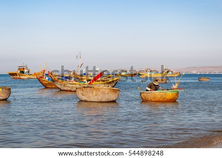 Fishing village, market and colorful traditional fishing boats near Mui Ne, Binh Thuan, Vietnam. Early morning, fishermen float to the coast with a catch.