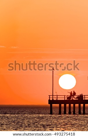 Fishing while the sunset sets of the sea, Melbourne Bay, Australia