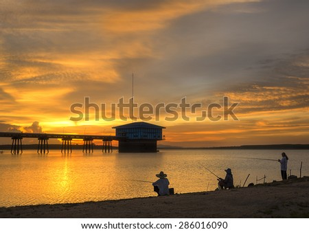 Fishing with reservoir over sunset and Silhouettes landscape view sunset Water reflection - stock photo