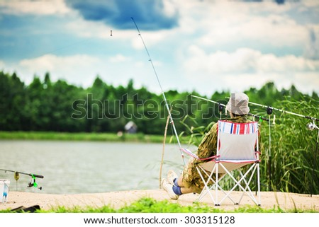 Fishing with spinning from shore of the lake - stock photo