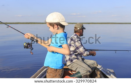 Fishing with spinning. Grandfather and grandson fishing together on a spinning sitting in a boat on a river - stock photo