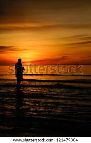 Fishingman and sunset - stock photo