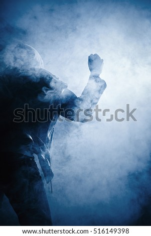 Fist and hand of a man in leather jacket and hoodie in fog in the backlight