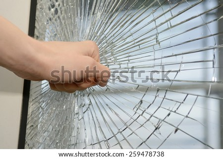 Fist demolishing windowpane