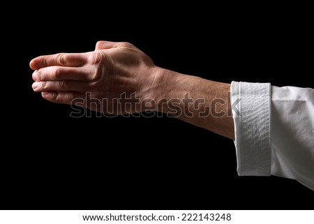 Fist. Hand fighter karate on the black background  - stock photo