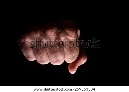 Fist lit from below isolated on a black background. - stock photo