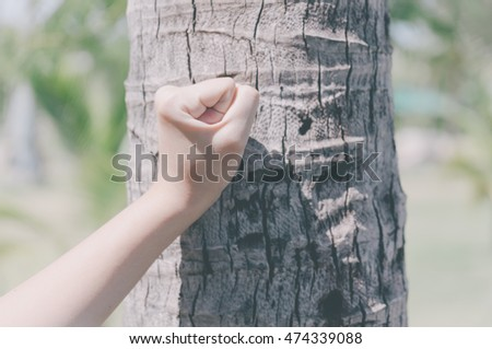 Fist of a young girl holding a coconut tree, pastel color