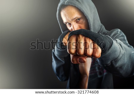 fist of young dangerous man closeup. strong serious  athletic man wearing hoodie shirts standing in boxing pose - stock photo