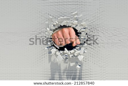 Fist punching through a brick wall - stock photo