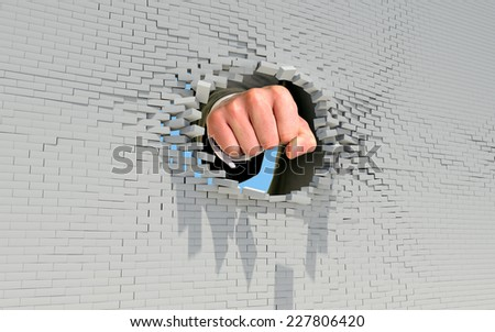Fist punching through brick wall. Business concept - stock photo