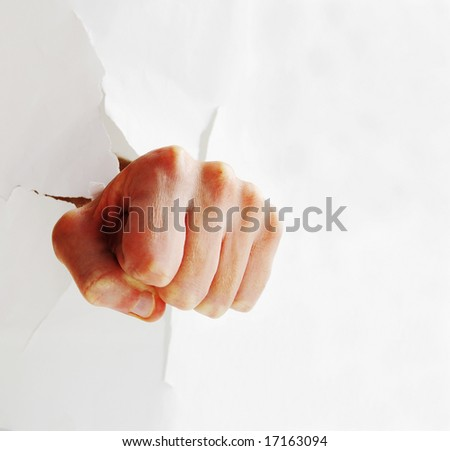 Fist punching through paper creating a torn hole