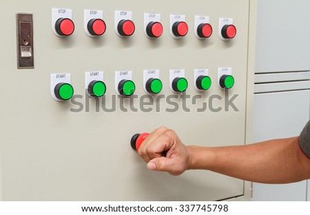 Fist smash touch on red emergency stop switch and reset on control panel for control machine - stock photo
