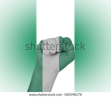 Fist wrapped in the flag of Nigeria and flag in the background - stock photo