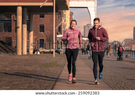 Fit active young couple running on a seafront promenade with the athletic woman leading the way approaching the camera in a healthy lifestyle concept