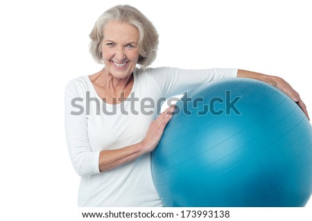 Fit aged woman holding big blue exercise ball - stock photo