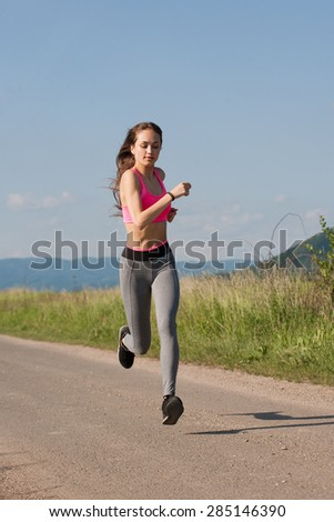 Fit and agile young brunette woman running outdoors in the sunshine.