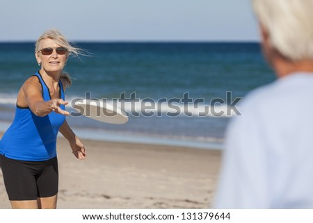 Fit and healthy senior man & woman couple playing with frisbee on a deserted beach by the sea - stock photo