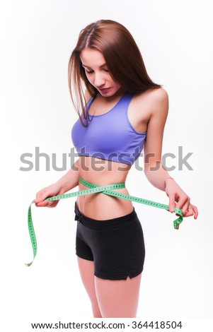Fit and healthy young lady measuring her waist with a tape measure in centimeters and millimeters. Girl look at measure. Isolated image on white. - stock photo