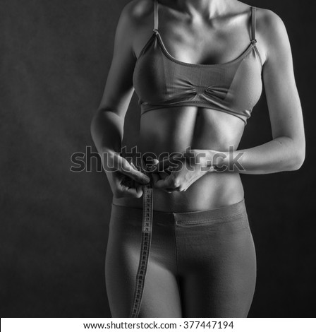Fit and healthy young woman measuring her waist with a tape measure. Black and white toning.