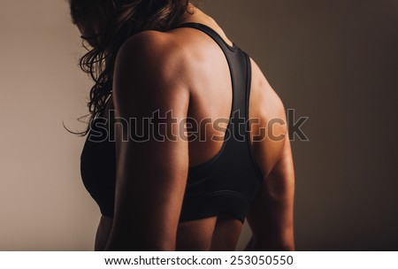 Fit and muscular woman in sports bra standing with her back towards camera. Rear view of fitness female with muscular body. - stock photo