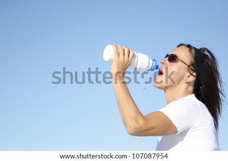 Fit and sporty mature woman drinking water as refreshment after exercising outdoor, isolated with clear blue sky as background and copy space.