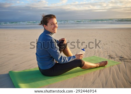Fit and sporty young woman sitting on her yoga-mat on the beach at sunrise looking back you smiling - stock photo