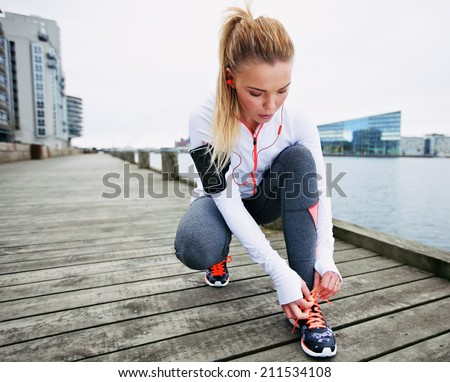 Fit and sporty young woman tying her laces before a run. Female runner tying her shoelaces while training outdoor. - stock photo