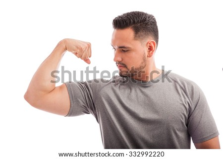 Fit and strong young man flexing his arm and showing his muscles on a white background