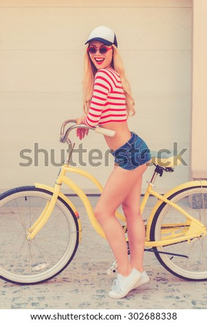 Fit and trendy. Side view of cheerful young woman smiling and looking at camera while standing near her bicycle against the garage door - stock photo