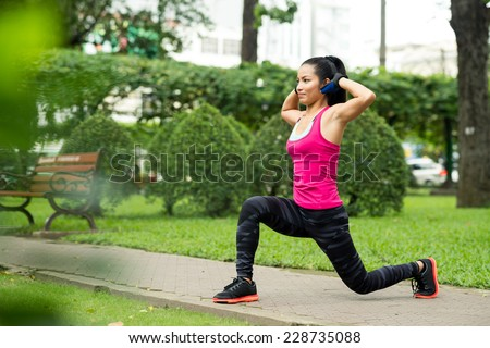 Fit Asian woman doing lunge exercise in park  - stock photo